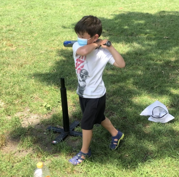 Child in mask playing tee-ball
